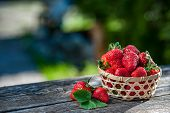Juicy Strawberries In A Wicker Basket Wooden Table, Against The Backdrop Of A Beautiful Background G poster