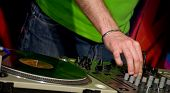 A detail of a gramophone disc with a DJ�?�´s hand
