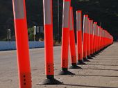 A line of delineators cone off a traffic lane for construction.