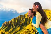 Travel couple fun piggyback at Na Pali Kauai Hawaii vacation adventure. Happy young Asian woman and  poster