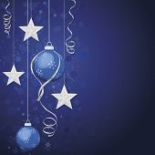 Blue ornaments and silver stars on deep blue background. Defocused background effect with snowflakes