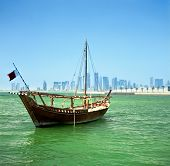 A traditional Arab dhow of the common Shuw'ai type moored in Doha Bay, Qatar, with the city's modern