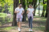 Young Couple Fitness In Sportswear Running Together In Park . Sport Man And Woman Jogging Outdoors I poster
