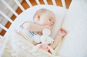 Baby Sleeping In Co-sleeper Crib Attached To Parents Bed poster