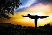 image of virabhadrasana  - Man silhouette doing virabhadrasana III warior pose with tree nearby outdoors at sunset background - JPG