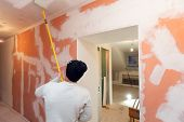 Worker Is Painting The Ceiling By Paint Roller In Corridor  An Apartment Is Inder Construction, Remo poster