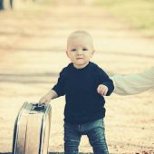 Small Boy Carry Retro Suitcase On Natural Landscape. Child Travel For Vacation With Bag With Mothers poster