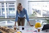 Portrait of blonde young Caucasian female architect looking at camera at desk in modern office. She  poster