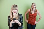 stock photo of raunchy  - Upset mom with happy teen on mobile phone - JPG