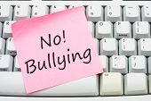 stock photo of stop bully  - A computer keyboard with a sticky note saying no bulling Stop internet bullying - JPG