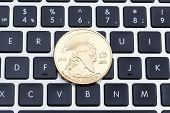 Cryptocurrency Physical Titan Bitcoin Coin On Black Computer Keyboard. poster