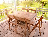 Set Of Wooden Table Dining And Chairs On Balcony Terrace With Front Yard Green Grass And Summer Gard poster