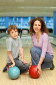 hijo y madre joven hermosa tener bolas rojas y azules y siéntese en el piso en club de bowling