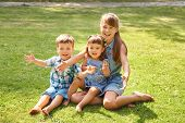 Playful Children Outdoors In The Summer On The Grass In A Backyard poster