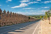 Medieval stone wall near a modern road