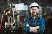 Waist Up Portrait Of Bearded Factory Worker Wearing Hardhat Looking At Camera While Standing In Work poster