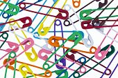 lots of colorful safety pin lying on a white background