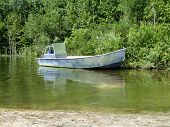 metal fishing boat anchored on shore
