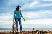 A Woman On The Eve Of The Holiday Earth Day Provides Volunteer Assistance In Cleaning The Coastal Ar poster
