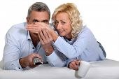 Woman covering her husband's eyes during a scary film