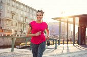Smiling sporty woman running outdoors. Latin young woman jogging in the city street at susnset. Happ poster