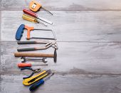 Screwdriver,hammer,tape Measure And Other Tool For Construction Tools On Gray Wooden Background With poster