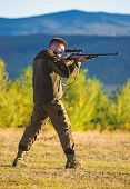 Man Rifle For Hunt. Hunter Khaki Clothes Ready To Hunt Hold Gun Mountains Background. Hunter With Ri poster