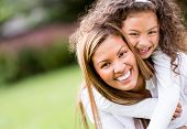 Happy mother and daughter laughing together outdoors