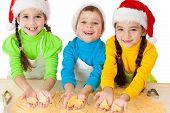 Tres niños sonrientes que muestra masa