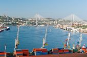 container terminal at russian port Vladivostok against the downtown and new bridge over Golden Horn