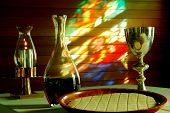 stock photo of eucharist  - The bread and wine used in Chrsitan religious service of the Eucharist backed by the stained glass image of Jesus cast onto a wall - JPG