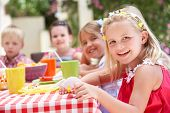 Group Of Children Enjoying Outdoor Tea Party