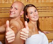 Happy smiling couple holding their thumbs up in a sauna