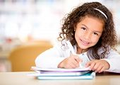 Cute little girl studying at the library and smiling