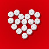 Pills in heart arrange on red background