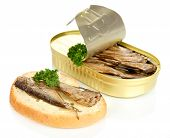 Open tin can with sardines and tasty sandwich, isolated on white