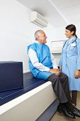 Doctor talking to senior patient before a bone density measurement