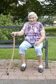 Smiling Senior Woman Sitting On Park Bench With Cane