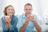 Content middle aged couple sitting on the couch having coffee smiling at camera at home in the living room