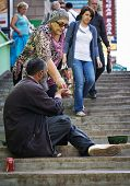 MOSCOW - AUGUST 8: Woman gives alms to beggar old man. In Moscow, Russia, August 8, 2013. 11.2 perce