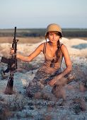 Young Beautiful Female Soldier Dressed In A Camouflage With A Rifle