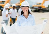 stock photo of real-estate-team  - Female architect at a construction site holding blueprints - JPG
