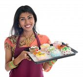 Happy Traditional Indian woman in sari baking bread and cupcakes, wearing apron holding tray isolated on white.