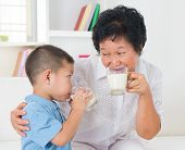 Drinking milk. Happy multi generations Asian family drinking milk at home. Beautiful grandmother and grandson, healthcare concept.