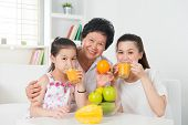 Asian family drinking orange juice. Happy Asian grandparent, parent and grandchild enjoying cup of fresh squeeze fruit juice at home.