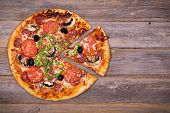 Pepperoni pizza with sliced vegetables on rustic, vintage style wood background