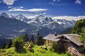 stock photo of chalet  - Idyllic view over the Swiss Alps with a alpine chalet in the foreground - JPG