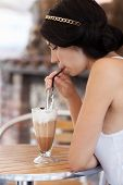 Brunette Girl Drinking Cappuccino In A Cafe
