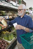 Senior man with shopping list at vegetable rack in supermarket