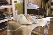 Closeup of wrapped shoes on worktable in traditional shoemaker workshop